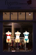 Illuminated mannequins display of lingerie stylish underwear in ladies clothing shop window, Lubeck, Northern Germany