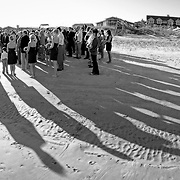 Long shadows are seen during a wedding ceremony at Litchfield Beach in this black and white photograph.  ©Travis Bell Photography