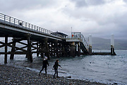 Children throwing stones into the sea next to Beaumaris Pier, on 17th of February 2020 in Beaumaris, Anglesey, North Wales, United Kingdom. The pier spans out into the Menai Straits a narrow 25 Km long stretch of shallow tidal water that separate the island of Anglesey  and the mainland of Wales. There are two bridges across the water.