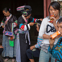 Lu Deqing and her friends dress for an outing. In her youth, Lu says, her mother would wear the elaborate headdress of the Buyi people on a daily basis, even while working at home or in the field. Village youth of today show little interest in the traditions of their parents. They want to get out of the village and experience the life they see on TV, get jobs and make money. The women lament the passing of the old traditions: hand weaving, fine embroidery, and the mountain songs.