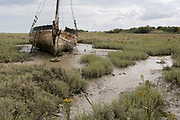 A low-tide landscape of poetry and sentences forming 'Graveyard of Lost Species', an boat artwork created by by artists and commissioned by Arts Catalyst, at low-tide on the Thames estuary, at Leigh creek, on 10th September 2019, in Leigh-on-Sea, Essex, England. The project celebrates the local tradition of wrecking boats on the salt marsh, its decaying memory of what has changed or passed. The boat is the 'Souvenir', a 39-foot Thames 'bawley' (1933) which once served the local fish trade in nearby Southend-on-Sea.