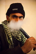 Atala Mohammed smokes hookah at his family's home in Umm Sayhoun, the bedouin village just outside Petra, Jordan.