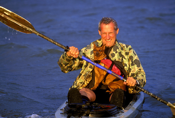 Stock photo of a man paddling his kayak with a dog on his lap