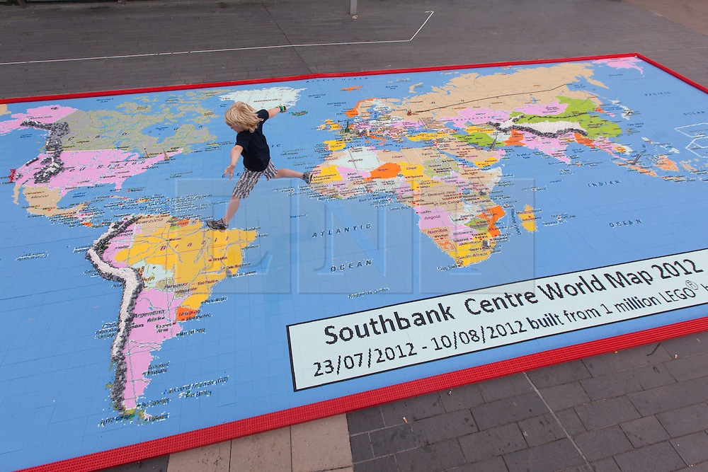 © licensed to London News Pictures. London, UK 13/08/2012. A child jumping on a giant map of the world, measuring 12 by 5 metres, made from over a million Lego bricks by members of public and designed by Duncan Titmarsh for the Festival of the World at Southbank Centre. Photo credit: Tolga Akmen/LNP
