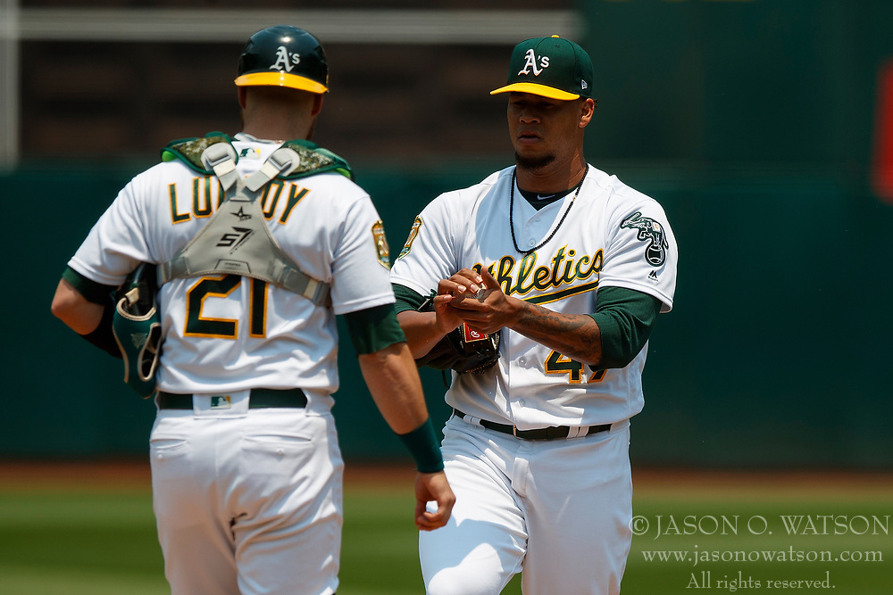 OAKLAND, CA - JULY 01:  Jonathan Lucroy #21 of the Oakland Athletics talks to Frankie Montas #47 during a mound visit during the first inning against the Cleveland Indians at the Oakland Coliseum on July 1, 2018 in Oakland, California. The Cleveland Indians defeated the Oakland Athletics 15-3. (Photo by Jason O. Watson/Getty Images) *** Local Caption *** Jonathan Lucroy; Frankie Montas