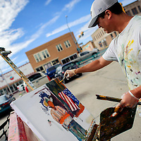 071414       Adron Gardner/Independent<br /> <br /> Chris Easley paints a scene of downtown at the Chamber of Commerce parking lot in Gallup Monday.