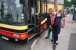 Secondary school girls boarding coach for school trip,