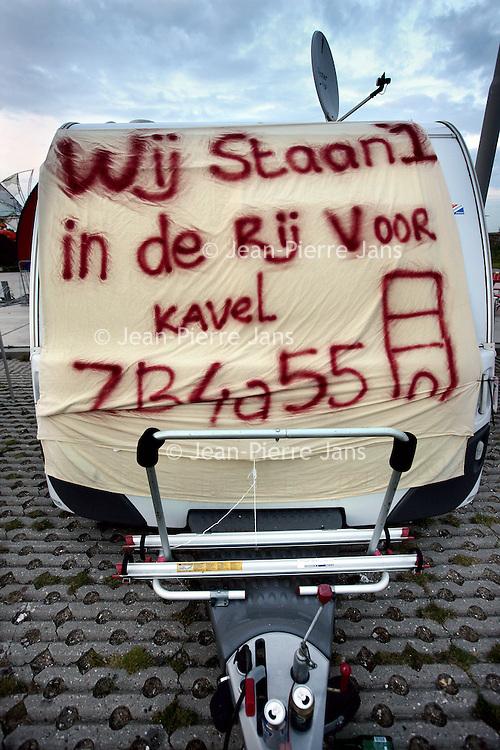 Nederland, Amsterdam , 1 oktober 2014.<br /> De rij caravans met mensen die een zelfbouwkavel willen kopen op het Zeeburgereiland wordt steeds groter.<br /> Sommige staan al een paar weken in de wachtrij totdat ze een kavel mogen kopen. Pas volgende week zaterdag gaan de kavels pas in de verkoop, maar wie weg gaat, verliest zijn plek in de rij.<br /> Een van de kampeerders staat er al een tijdje in zijn caravan: 'Ik ben hier behoorlijk vroeg gaan staan, want er is één kavel waar ik echt geïntresseerd in ben. Er hoeft er maar een eerder te zijn en dan ben je 'm kwijt.'<br /> De wachtende kopers vinden het best gezellig op het terrein: 'Je ontmoet een soort van je toekomstige buren als het zo doorgaat. Dat geeft een apart campinggevoel en we barbecuen samen.'<br /> Een probleempje, als je weggaat ben je je plek kwijt. 'Als je moet werken moet je zorgen dat er iemand anders op je plek zit. Ik had hier eerst helemaal geen zin in, maar het is toch wel een bizar avontuur.'<br /> Foto:Jean-Pierre Jans