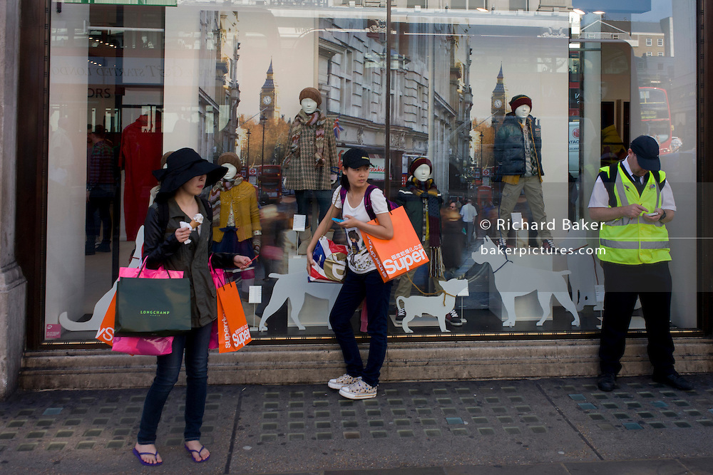Spending foreign shoppers stand outside an Oxford Street shop window showing a London landscape.