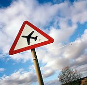 The 'Red Arrows', Air Force aerobatic team train over the skies of Lincolnshire, above 'low flying' warning road sign.