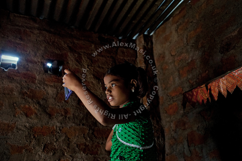 Poonam, 10, is looking at the mirror while standing inside her family's newly built home in Oriya Basti, one of the water-contaminated colonies in Bhopal, central India, near the abandoned Union Carbide (now DOW Chemical) industrial complex, site of the infamous '1984 Gas Disaster'.
