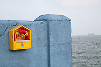 Ringbouy on a wall in Dun Laoghaire Dublin Ireland boat in the distance on the sea