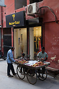 A fruit vendor outside a modern upscale shop in the trendy village of Sharpur Jat now home to expensive couture and the burgeoning fashion industry. New Delhi, India