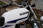 Badge on a Suzuki motorcycle in De Hui, Jilin province is replaced upside down. Mistakes with English written language is common in China.