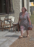 Living History event. Woman in 1940s clothing carrying kettle and water jug to make tea.