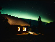 Green aurora arcing above cabin on Colorado Lake, Broad Pass, night of March 23-24, 2001, Alaska.