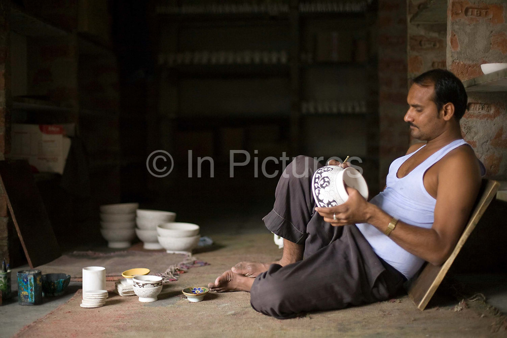 A Potter paints a clay bowl at a factory in Sanganer, Jaipur, India
