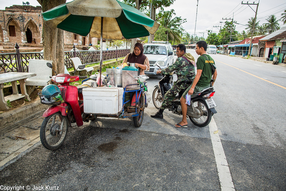 24 OCTOBER 2012 - PATTANI, PATTANI, THAILAND:  Thai soldiers buy ice cream snacks from a Muslim vendor in Pattani. More than 5,000 people have been killed and over 9,000 hurt in more than 11,000 incidents, or about 3.5 a day, in Thailand's three southernmost provinces and four districts of Songkhla since the insurgent violence erupted in January 2004, according to Deep South Watch, an independent research organization that monitors violence in Thailand's deep south region that borders Malaysia. Muslim extremists are battling the Thai government and its symbols, like schools and Buddhist facilities.    PHOTO BY JACK KURTZ