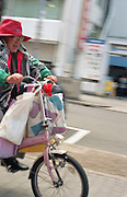 A woman riding a bicycle in trendy Sakae on the official 2,672nd anniversary of Japan.