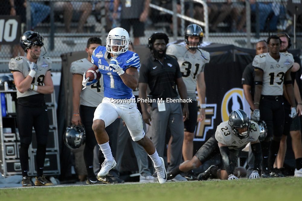 Memphis running back Tony Pollard (1) rushes for a 66-yard touchdown after breaking a tackle attempt by Central Florida defensive back Tre Neal (23) during the second half of the American Athletic Conference championship NCAA college football game Saturday, Dec. 2, 2017, in Orlando, Fla. Central Florida won 62-55. (Photo by Phelan M. Ebenhack)