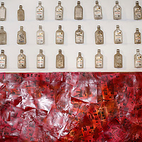 """Vodka bottles and alcohol advertisements adorn a wall in the """"Exposure"""" exhibit at Art123 Gallery in Gallup Thursday."""