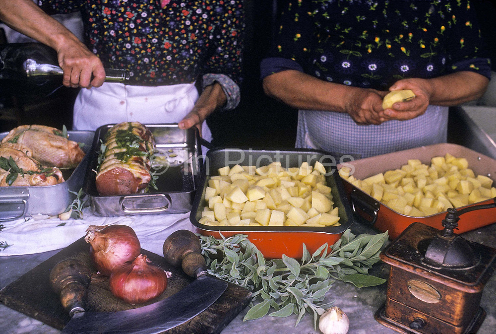 Women cooks prepare a lunch of Loin of Pork  and potatoes on the Frescobaldi wine estate, italy
