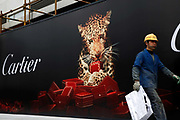 A construction worker walks past a large luxury goods advert in Shanghai, China on 24 March, 2011.  Some local governments in China are instituting limits or banning outdoor advertisements for luxury brands, in hopes of curbing increasing public awareness of the widening wealth gap.