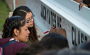 Members of the senior class sign a beam that will be included in the construction of Yates High School, April 20, 2017.