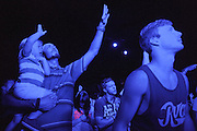 TRUSSVILLE, AL - AUGUST 27, 2013: Mason Rule (left) worships with his nephew during a service at The Basement, a Christian youth ministry widely known for its club atmosphere and large crowds. The worship gathering, held at the B-Studio in Trussville, was the first meeting since The Basement's founder Matt Pitt was arrested for impersonating a police officer on August 20, 2013. CREDIT: Bob Miller for The New York Times.