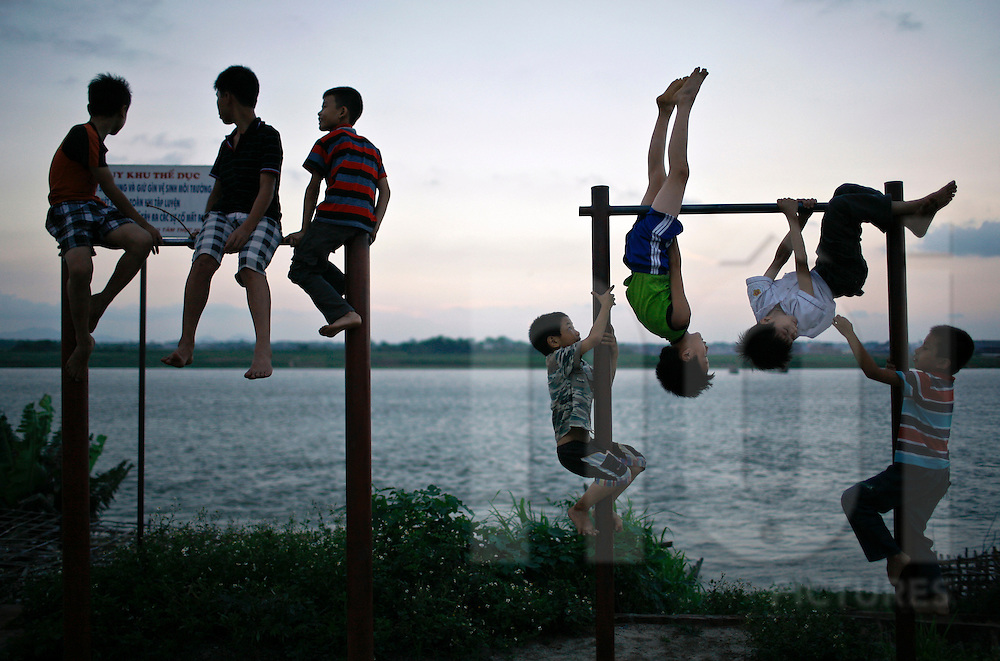 Young boys play together on metal structures and watch the sun set over Hanoi, Vietnam, Southeast Asia