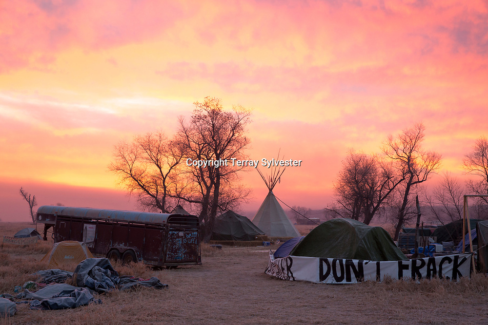A tipi and an anti-fossil fuels slogan are seen during a fiery sunrise over the opposition camp against the Dakota Access oil pipeline on November 14, 2016, North Dakota, United States.