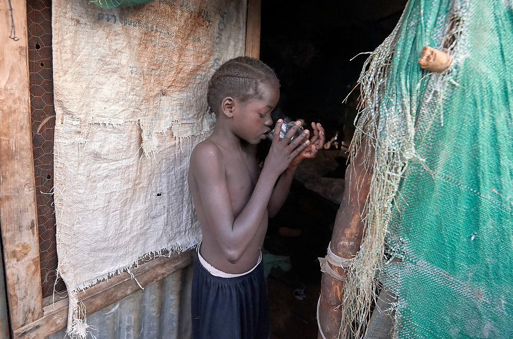 A girl drinks tea in the doorway of her family's shelter in a displaced persons camp at the Holy Family Catholic Church in Wau, South Sudan. The church has provided food, shelter material, and health care, and the presence of clergy and religious has fostered a sense of relative safety for the families who first occupied the church grounds when fighting enveloped the city in 2016.