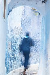 Man walking through blue doorway, Chefchaouen, Morocco