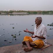 Guru Ramnat Gi doing his evening puja prayers on the banks of the polluted Yamuna, near Nigambodh Gath.