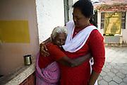 Parvati an elderly resident cuddles the manager Amudha at the Tamaraikulum Elders village, Tamil Nadu, India