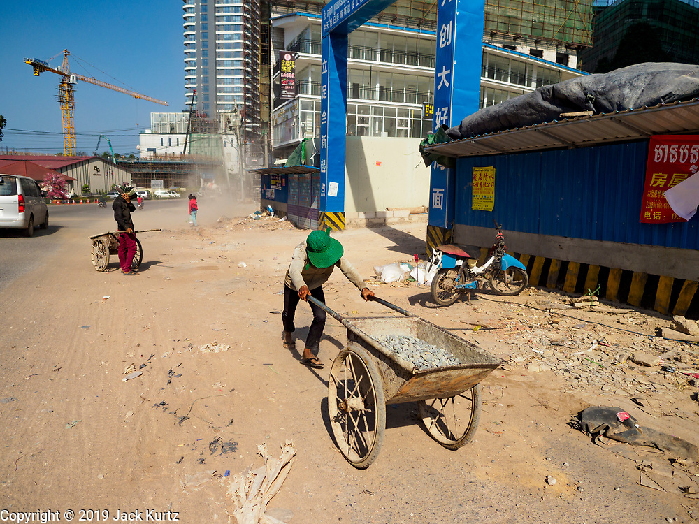 """15 FEBRUARY 2019 - SIHANOUKVILLE, CAMBODIA: A Cambodian laborer pushes gravel past a Chinese casino being built in Sihanoukville. There are about 80 Chinese casinos and resort hotels open in Sihanoukville and dozens more under construction. The casinos are changing the city, once a sleepy port on Southeast Asia's """"backpacker trail"""" into a booming city. The change is coming with a cost though. Many Cambodian residents of Sihanoukville  have lost their homes to make way for the casinos and the jobs are going to Chinese workers, brought in to build casinos and work in the casinos.      PHOTO BY JACK KURTZ"""