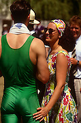 A young woman chats with a tall, athletic rower at the annual Henley Regatta, England. Fondling the man's rear, the girl smiles happily during this annual festival of high-society, serious rowing and general clowning around on the rural Thames. In 1829 a boat race challenge was held between teams representing the universities of Oxford and Cambridge. The venue chosen was a straight stretch of the Thames at the small town of Henley-on-Thames. Now held July and is one of the main dates on the sporting calendar and social season for the upper-classes.