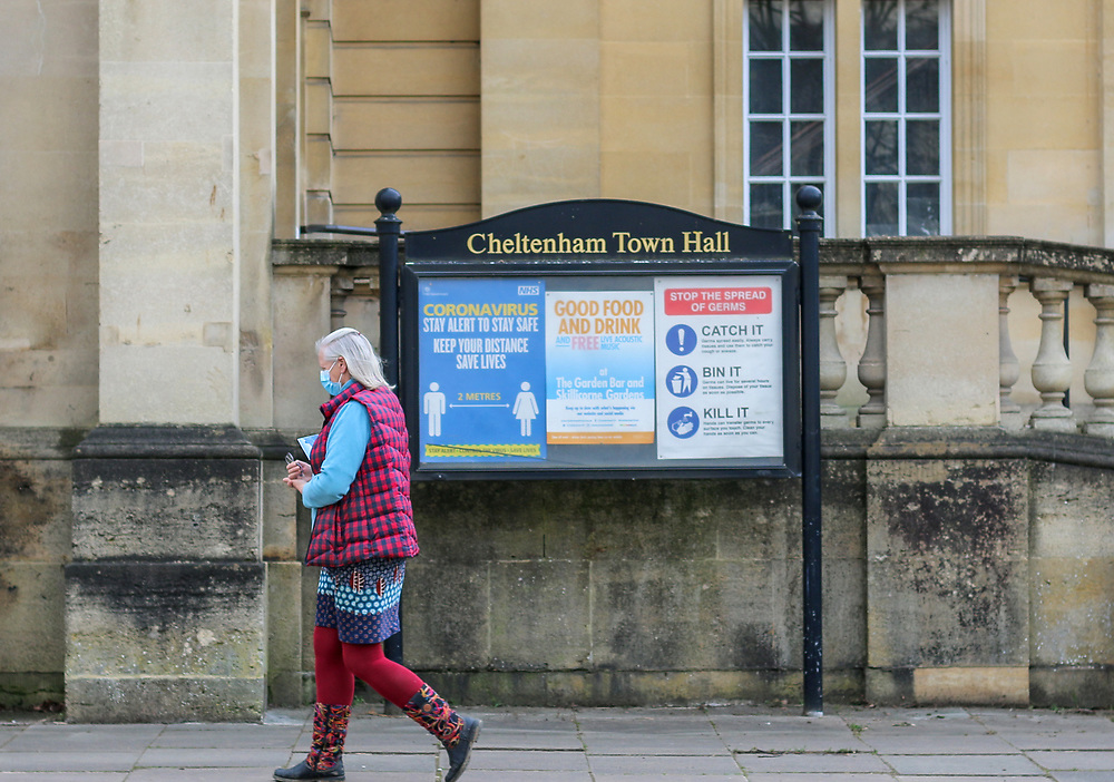 24th February, Cheltenham, England. A woman walks by the Cheltenham Town Hall wearing a mask during the third national lockdown.
