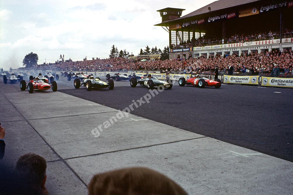 The start of the 1965 German Grand Prix at the Nurburgring with John Surtees (Ferrari - 7), Jim Clark (Lotus-Cimax - 1), Dan Gurney (Brabham-Climax - 5) and Lorenzon Bandini (Ferrari - 8) on the front row.. Photo: Grand Prix Photo