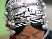 Close up of an Akha women's headdress, Muang Long, Luang Namtha province, Lao PDR. The headdress is made from hand forged silver, coins, handwoven cotton, market bought cotton, plastic beads, bamboo, cowrie shells and woollen tassels. Women would traditionally wear their headdress even while bathing, sleeping and working in the fields.
