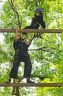 Town of Wallkill, New York - Ninja Warrior Day Camp head instructor Andrew Benskie helps Grace Ring climb a ladder on ropes course at Ring Homestead Camp on July 8, 2014.