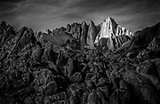 A shaft of sunrise light spotlights 14,505' Mt. Whitney, the highest point in contiguous United States, above the darkened rocks of the Alabama Hills.