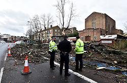 © Licensed to London News Pictures. 28/03/2016. London, UK. Police officers and tree specialists assess a tree that has been blown over at a bus stop in Clapham, south west London caused by high winds as Storm Katie hits the UK. Photo credit : Hannah McKay/LNP