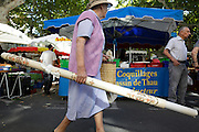 elderly woman walking with a plastic floor covering at an outdoors farmers market