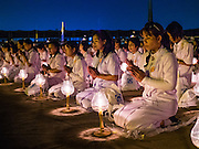 """22 FEBRUARY 2016 - KHLONG LUANG, PATHUM THANI, THAILAND:  People pray and meditate on the plaza in front of the chedi during Makha Bucha Day services at Wat Phra Dhammakaya.  Makha Bucha Day is a public holiday in Cambodia, Laos, Myanmar and Thailand. Many people go to the temple to perform merit-making activities on Makha Bucha Day, which marks four important events in Buddhism: 1,250 disciples came to see the Buddha without being summoned, all of them were Arhantas, Enlightened Ones, and all were ordained by the Buddha himself. The Buddha gave those Arhantas the principles of Buddhism, called """"The ovadhapatimokha"""". Those principles are:  1) To cease from all evil, 2) To do what is good, 3) To cleanse one's mind. The Buddha delivered an important sermon on that day which laid down the principles of the Buddhist teachings. In Thailand, this teaching has been dubbed the """"Heart of Buddhism."""" Wat Phra Dhammakaya is the center of the Dhammakaya Movement, a Buddhist sect founded in the 1970s and led by Phra Dhammachayo.     PHOTO BY JACK KURTZ"""