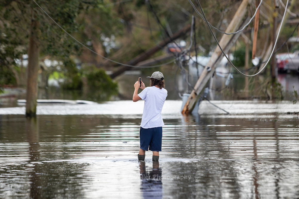 A day after Hurricane Ida turned through Louisiana Jordan Cook walks down flooded Clayton Road in Norco, La. to inspect the flood damage to his girlfriends grandparents home.