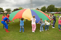 Group of children taking part in a parachute game at a Parklife summer activities event,