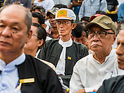 03 NOVEMBER 2015 - YANGON, MYANMAR: A man wearing a Democratic Party Myanmar hat and other people in downtown Yangon listen to speakers at a Democratic Party Myanmar campaign rally. The Democratic Party of Myanmar was established in the wake of the 1988 protests and contested the 2010 elections. The party is running candidates in several races for the Myanmar legislature.        PHOTO BY JACK KURTZ