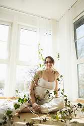 Pregnant woman sitting on floor with ivy