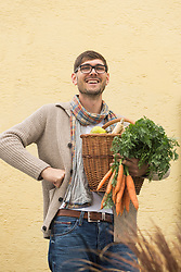 Portrait of a mid adult man holding basket full of vegetables and smiling, Bavaria, Germany
